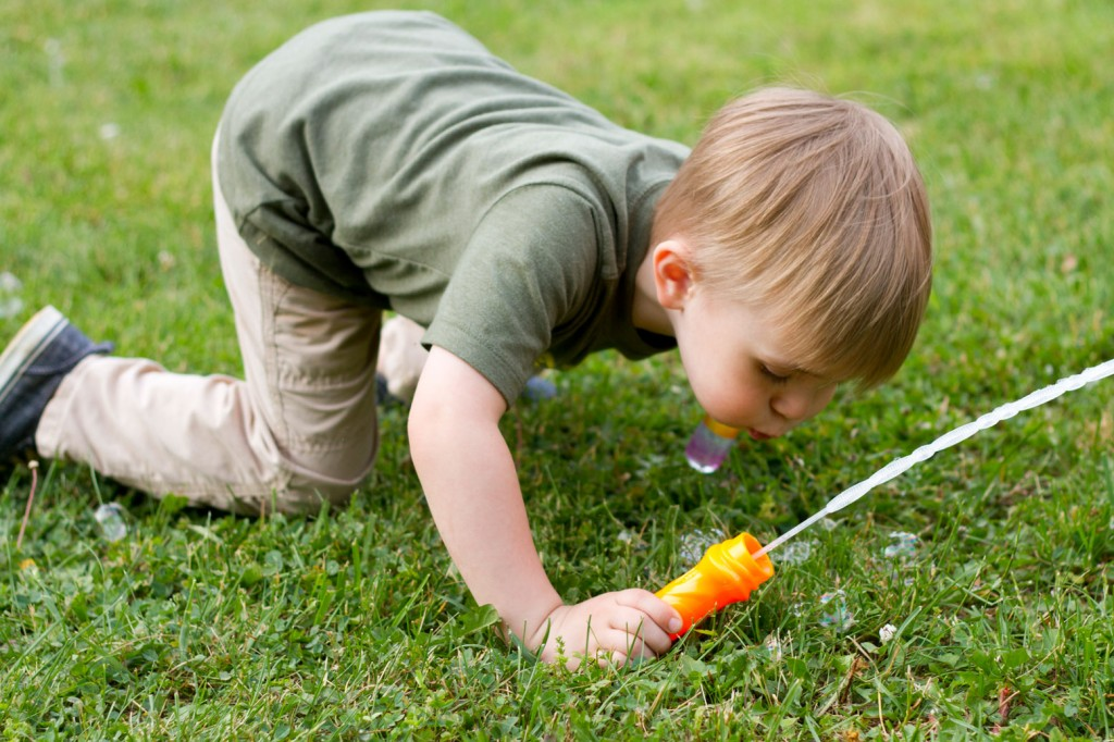 Sawyer blowing bubbles in the grass